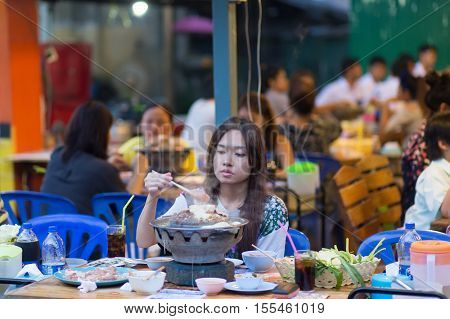 BANGKOK, THAILAND, SEPTEMBER 23, 2016 :Woman having traditional Thai Mookata barbecue in a Bangkok restaurant, Thailand