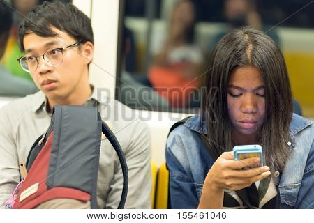 BANGKOK, THAILAND, SEPTEMBER 23, 2016 : Passenger using smartphone inside the public transportation in Bangkok, Thailand