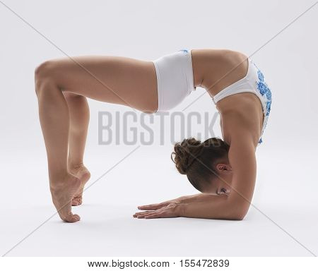 Photo of flexible girl posing while doing acrobatic stunt