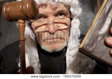 Judge. Senior judge in a courtroom striking the gavel