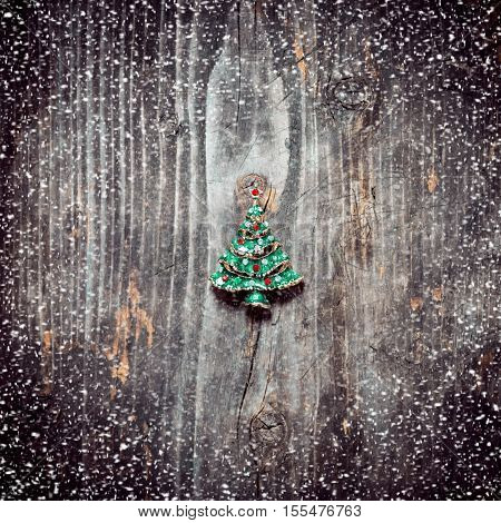 Christmas background. Pendant Christmas tree lies on the old wooden boards. Merry Christmas. Snowing.Toned image.