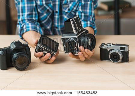 Unrecognizable blogger shows structure of retro camera. Different generation of camera comparison. Technology progress concept