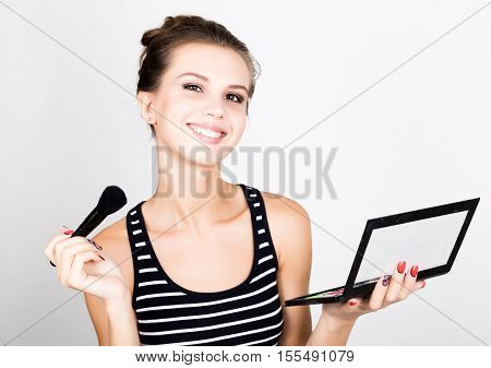 Female model applying makeup on her face. Beautiful young woman applying foundation on her face with a make up brush
