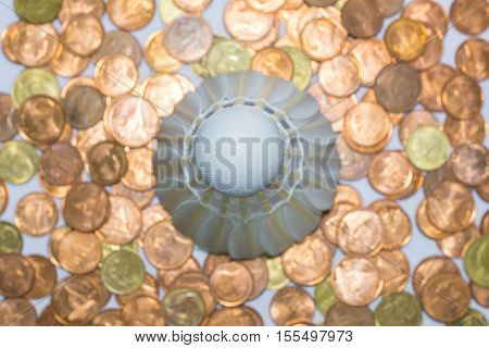 Background pile of coins with the shuttlecock on top.