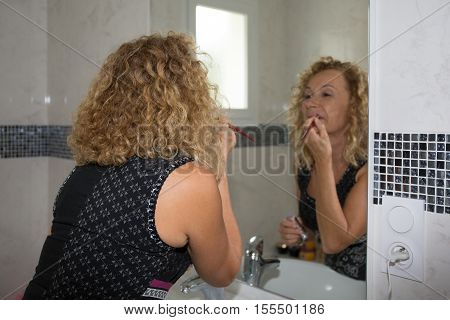Happy Woman Applying Gloss On Lips In Bathroom At Home