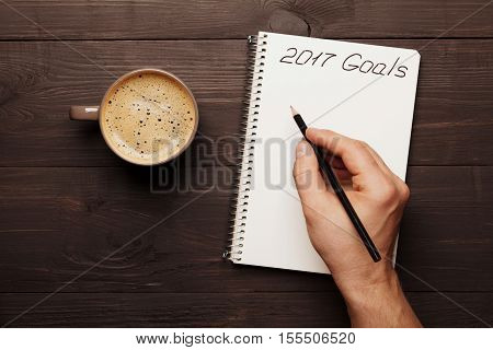 Cup of coffee and male hand writing in notebook goals for 2017. Planning and motivation for the new year concept. Top view.