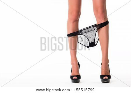 Female legs with panties down. Black underwear and shoes. When passion wakes. Seduction and sensuality.