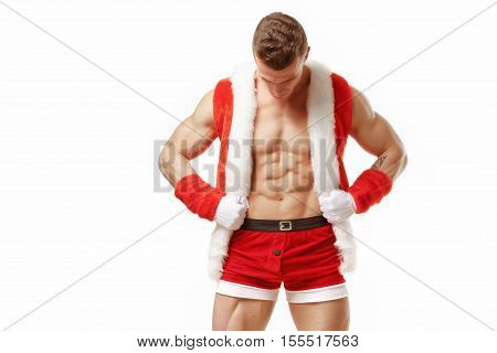 Muscular fitness man in a suit of Santa Claus. Fitness Santa Claus with perfect muscular body showing six pack abs. Strong Athletic Man Fitness Model Torso showing six pack abs. Santa Claus isolated