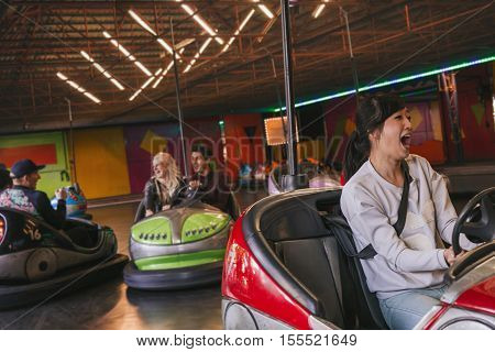 Group of friends having fun on bumper car ride in amusement park. Young man and woman having fun with bumper cars.