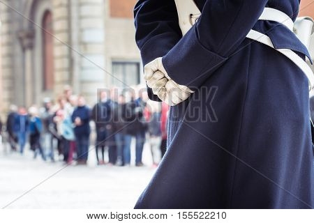 Close up of a Swedish Royal Guard's hands and costume with the people attending the change of guard in the background