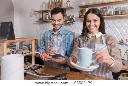 At the working place. Satisfied emotional waiters smiling and selling coffee while standing at the counter