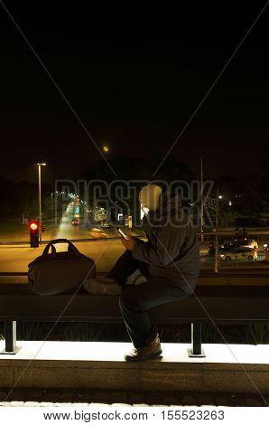 Terrorist using social media vertical shot. Night shot. Long exposure