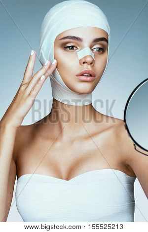 Young woman after plastic surgery touching her cheekbone. Photo of woman wrapped in medical bandages. Beauty concept