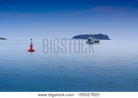 Floating red marine buoy and boat on blue sea gulf of Thailand with copy space.