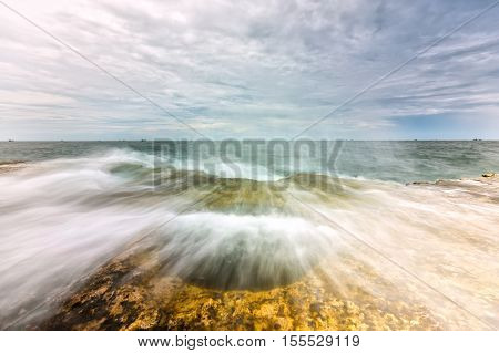 Wonderful Seascape with high waves hit large boulders create great water column represent the power of nature when high tides. It's great to watch the sea moments