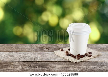 paper cup of coffee on natural outside background with copy space. Coffee on table on nature background. Takeaway coffee. Coffee to go. Coffee. Paper cup of coffee on table on bright background