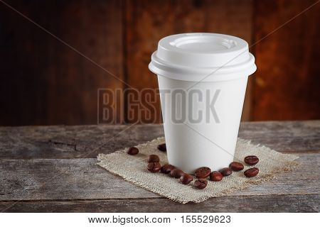 Paper cup of coffee and coffee beans on old wooden table with copy space. Takeaway coffee. Coffee to go. Coffee. Disposable cup of coffee with closed lid