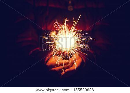 bright festive Christmas sparkler. Beautiful bright celebratory sparkler. Sparkler. Female hands holding bengal light. Woman holding bright festive Christmas sparkler in hand tinted photo. Sparkler - New Year's Eve