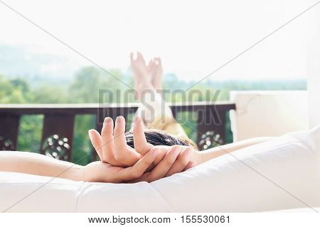 poster of Rear view of asian woman relaxing on a sofa and looking outside a green background view at home terrace. Relaxing concept.