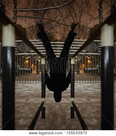 Man upside down on parallel bars on sport playground in yard at winter night, back view