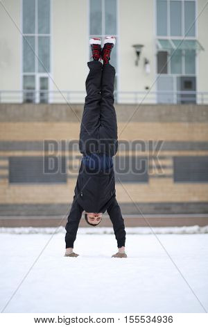 Man stands on hands upside down next to building at winter day
