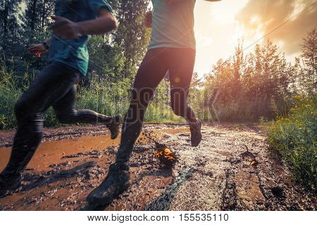 Two trail running athletes crossing the dirty puddle