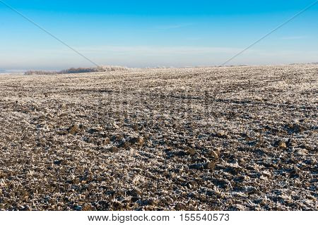 Landscape with agricultural fields covered with hoar-frost at autumnal season