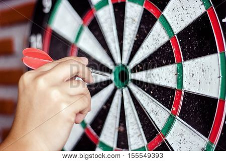 close up hand catch the red arrow push to target on dart game in lck target concept