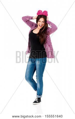 Cheerful teen girl with big red bow, isolated on white background. Full length portrait of beautiful crazy smiling brunette young woman screaming with mouth wide open.