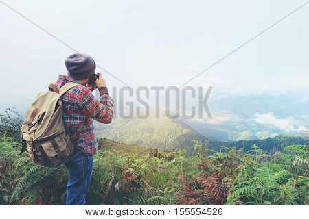 Photographer is taking a picture in mountains