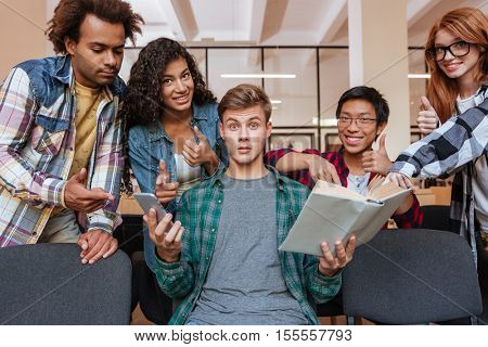 Group of happy students showing thumbs up standing around amazed boy with book and smartphone