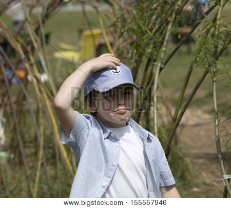Little boy stands near pond and has astonished and disbelieving look. Knocking on his head or thinking. The kid has pouting mouth and funny expression. Sunny, cheerful holiday atmosphere near the lake
