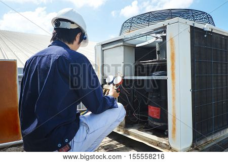 Technician is checking air conditioner in factory