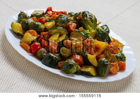 Fried vegetables on white plate with herbs and pepper