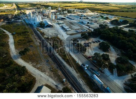 Aerial Over Texas Limestone Extraction Factory with RailRoad Tracks delivering minerals in and out of the factory. The Open Pit mine in the morning sun