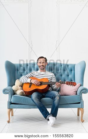 Let me sing a song. Positive joyful brunette man sitting in the middle of the sofa and playing the guitar while singing a song