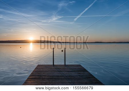 Quiet evening on the lake. Setting sun is reflected in water. Switzerland.