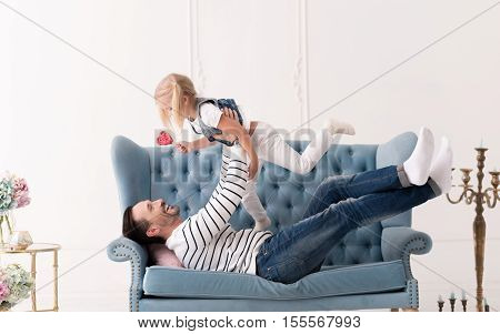 Happy moments. Positive delighted loving father lying on the sofa and looking at his daughter while lifting her up