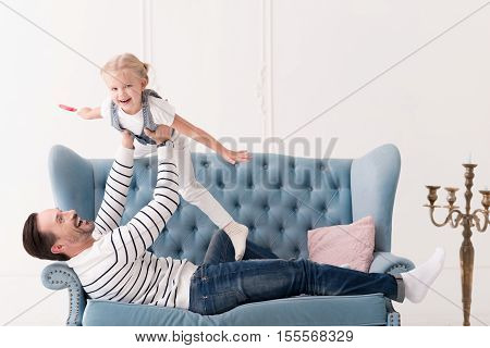 I love my father. Cute happy optimistic girl laughing and pretending to fly while being lifted by her father