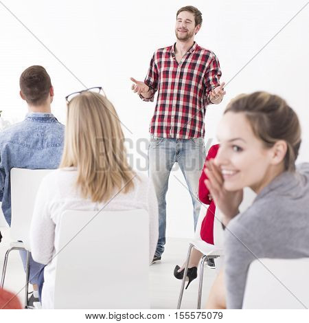 Young woman whispering to his friend during the manager presentation