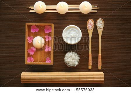 Spa set with nutrient cream and sea salt in spoons on wooden background