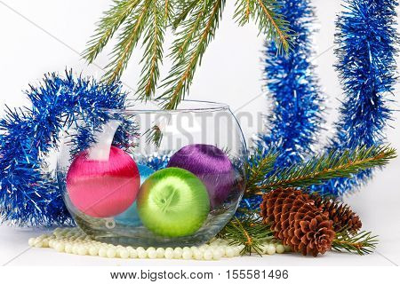Colored christmas balls in a glass vase among fluffy blue tinsel and fir-tree brunches on white background