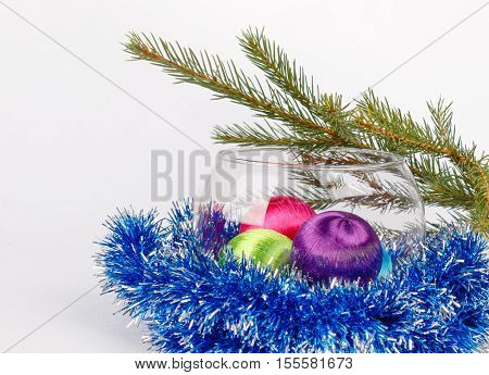 Colored christmas balls in a glass vase among blue tinsel on background of fir-tree brunches