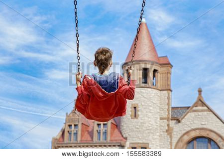 boy on a swing on a background an ancient fortress. the concept of childhood and dreams