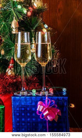 Two glasses of champagne on background christmas tree. Selective focus