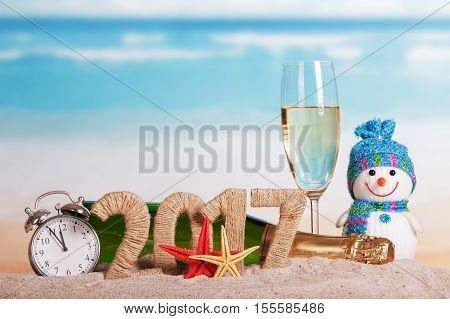 Figures 2017, a bottle of champagne and glass, snowman, alarm clock, starfish in the sand against the sea.