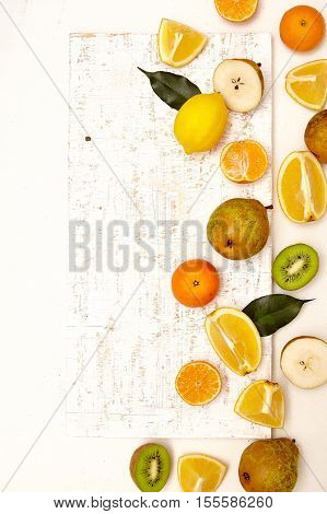 Colorful background with citrus fruits. Apple mandarin kiwi lemon pear on the white rustic wooden table. Copy space