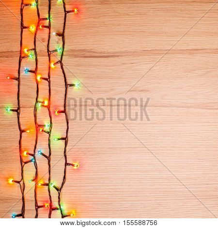Christmas lights of different colors on a wooden board