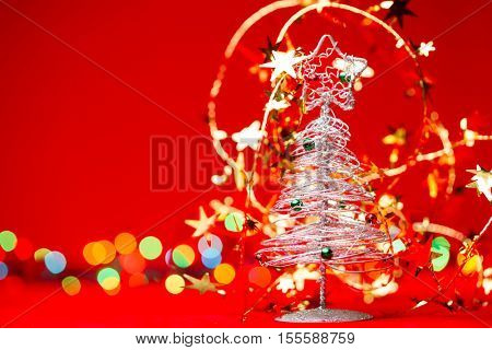 Small tabletop Christmas tree with golden tinsel and blurred christmas lights in background