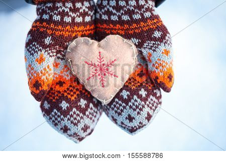 Woman wearing knitted mittens holding heart in cupped hands winter holidays concept